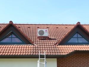 """Venkovní klimatizační jednotka """"schovaná"""" mezi střešními okny - klimatizace do ložnice rodinného domu."""